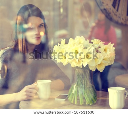 Young woman drinking tea sitting indoor in urban cafe. Cafe city lifestyle. Casual portrait of beautiful girl with spring flowers. Image toned and noise added. - stock photo
