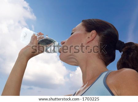 young woman drinking water after a workout