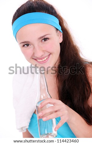 Young woman drinking water after fitness workout on white background