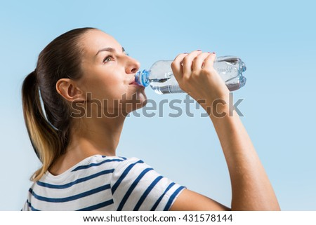 Young woman drinking water after jogging - stock photo