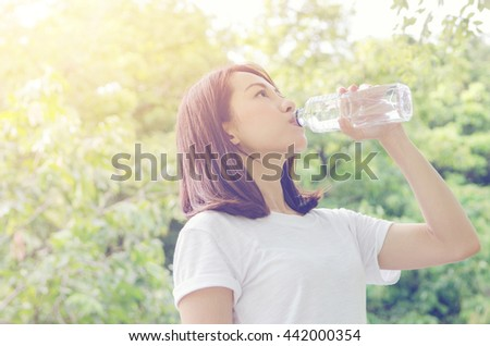 Young woman drinking water after jogging at summer green park. outdoor.