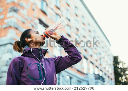 Young woman drinking water after running in city - stock photo