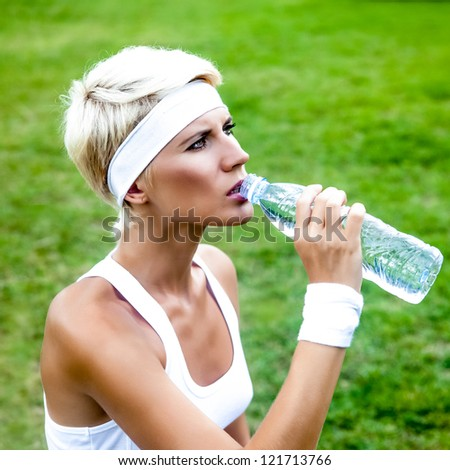 Young woman drinking water at workout outdoors
