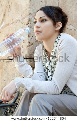Young woman drinking water from a plastic blue bottle while sitting down near an old stone wall, outdoors. - stock photo