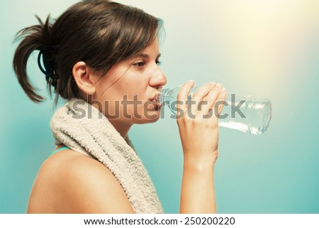 Young woman drinking water from bottle post processed with colour and filters.  - stock photo