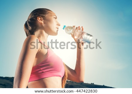 Young woman drinking water from plastic bottles after jogging. Girl quenches thirst after fitness outdoors. Lose weight. Healthy lifestyle. - stock photo
