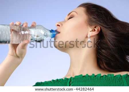 Young woman drinking water from the bottle
