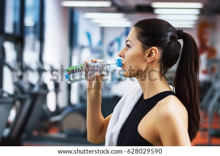 Young woman drinking water gym stock photo 628029590 shutterstock young woman drinking water in the gym sciox Choice Image