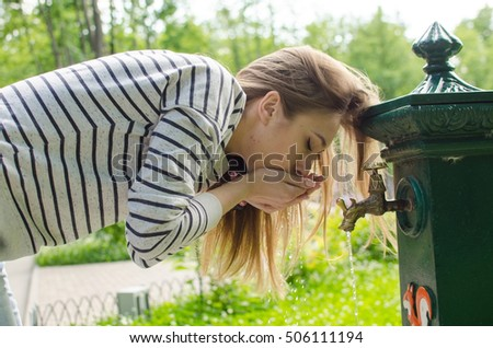 Young woman drinking water in the park