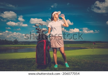 Young woman drinking water on a golf field  - stock photo
