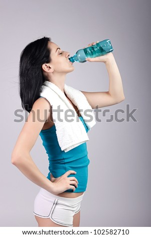 Young woman drinking water with eyes closed.Brown background. - stock photo