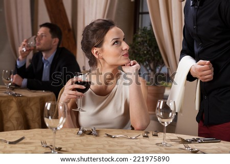 Young woman drinking wine flirting with waiter - stock photo