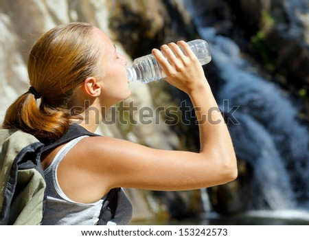 Young woman drinks water by waterfall.