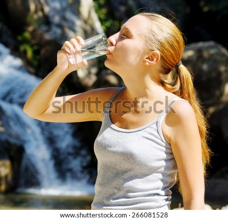 Young woman drinks water by waterfall. - stock photo