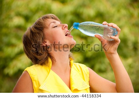 Young woman drinks water from bottle, has closed from eye pleasure