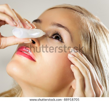 Young woman dripping eyes at home