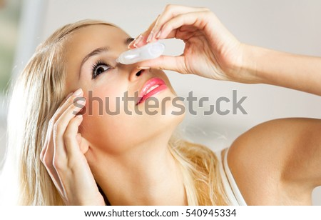 Young woman dripping eyes at home. Healthcare concept.
