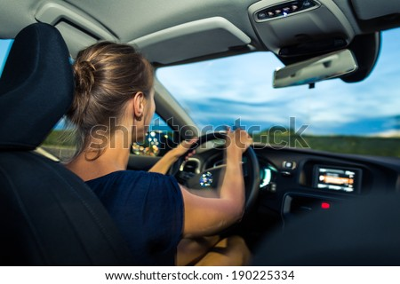 Young, woman driving a car at dusk, going home from work (long exposure used -> slighlty motion blurred image - give sense of speed/movement) - stock photo