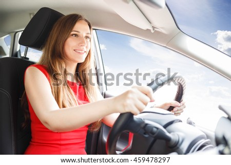Young woman driving a car. Fast delivery or taxi concept background