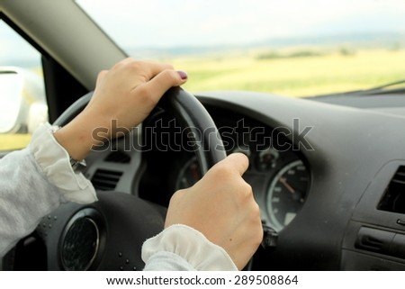 Young woman driving car - hands of a driver on steering wheel of a car - stock photo