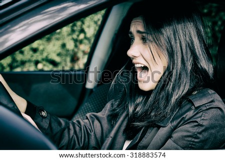 Young woman driving car scared about accident - stock photo