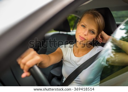 Young woman driving her car, on her way home from work - doing the daily commute - stock photo