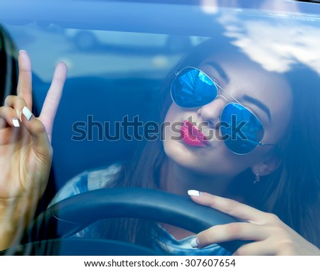 Young woman driving her car.Stylish student girl in car.Summer fashion close up portrait elegant beautiful woman driving her car in urban city.Funny Female driver in swag sunglasses and red lipstick - stock photo