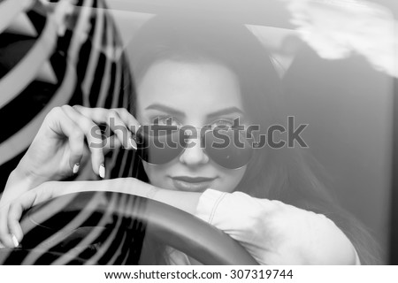 Young woman driving her car.Stylish student girl in car.Summer fashion close up portrait of elegant beautiful woman driving her car in urban city.Black and white image. - stock photo