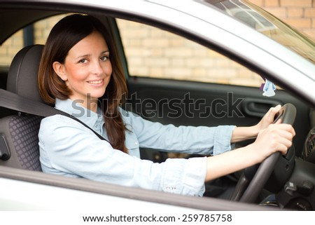 young woman driving her car with her seatbelt fastened  - stock photo