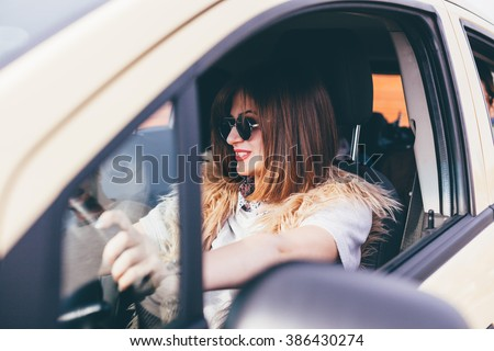 Young woman driving her new car - stock photo