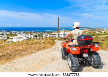 Young woman driving quad on gravel road on Paros island, Greece