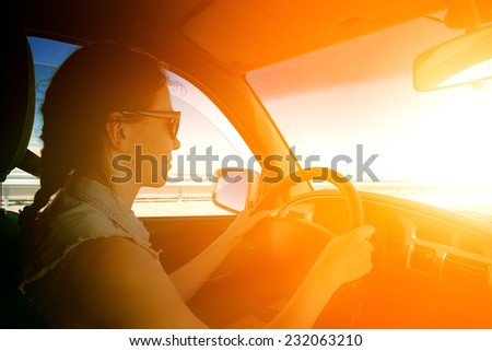 young woman driving to sunset - stock photo