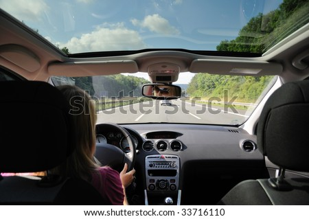 Young woman driving with her car - stock photo