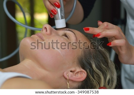 young woman during cosmetic facial treatment