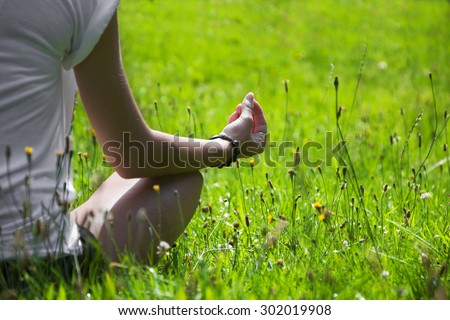Young woman during relaxation and meditation in park meditation session. Frame shows half of body. - stock photo