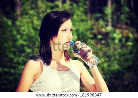 Young woman during warm, sunny day, drinking water to cool down. Pretty girl holding bottle of cold water next to her lips and pouring drink to her mouth.