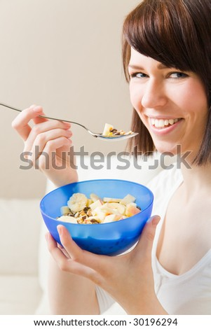 Young woman eating a bowl of muesli - stock photo
