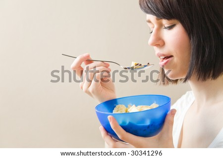 Young woman eating a bowl of muesli