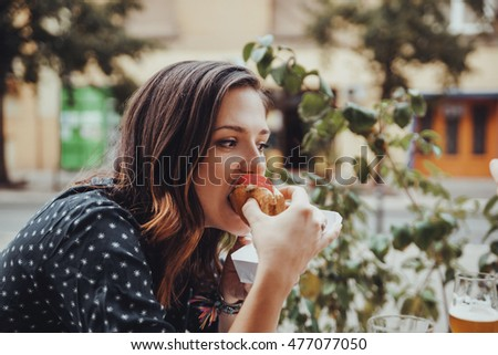 Young Woman Eating A Hotdog