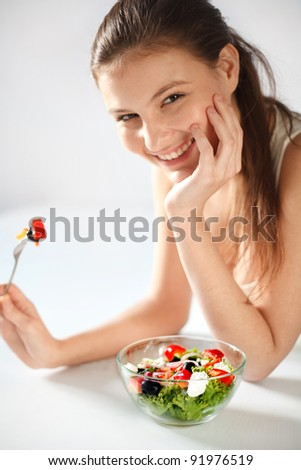 Young woman eating a salad while looking at the camera
