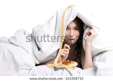 young woman eating cake under cover on white background - stock photo