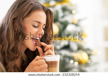 Young woman eating candy with latte macchiato near christmas tree