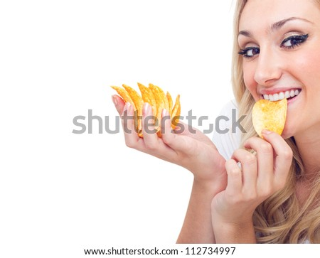 Young woman eating chips, studio-shot
