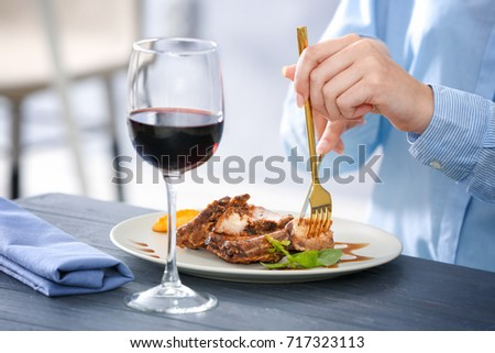 Young woman eating delicious ribs in restaurant