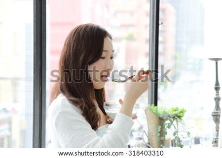 Young woman eating granola breakfast at home
