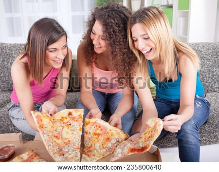 young woman eating pizza at home