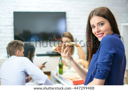 Young woman eating pizza while sitting with her friends at home. - stock photo