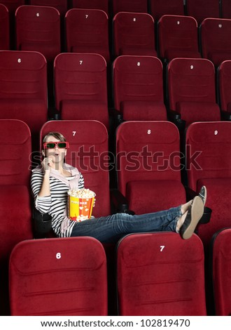 Young woman eating popcorn in 3D movie theaterthea