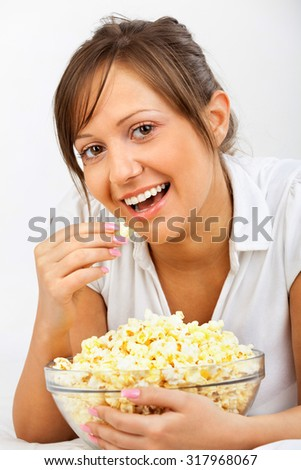 Young woman eating popcorn isolated on white background
