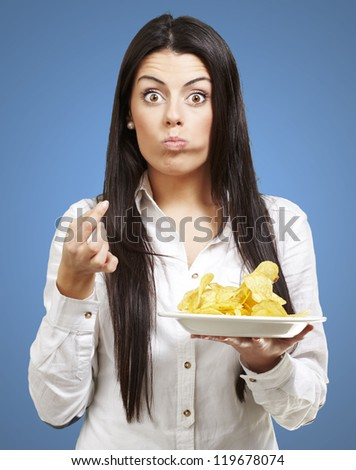 young woman eating potato chips against a blue background - stock photo
